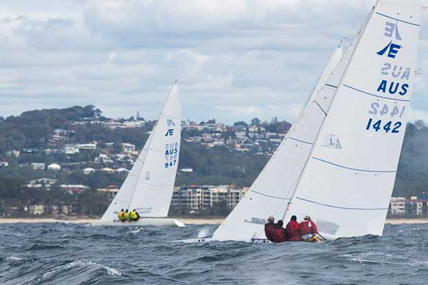 The yellow jerseys of Magpie in against the beach, with Iron Lotus in behind one of the many waves on offer today. - 2017 Etchells Australasian Championship © Alex McKinnon Photography http://www.alexmckinnonphotography.com