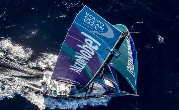 Day 14, Leg 2, Lisbon to Cape Town, on board AkzoNobel. Brad Farrand in an alomost Chameleon like state with the matching wet weather gear up the mast. He is doing a rig check before the winds start to pick up later today – Volvo Ocean Race © James Blake / Volvo Ocean Race